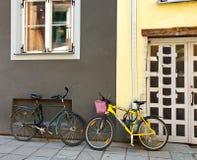 Велосипед на улице около желтого стена дома с образом жизни корзины для товаров на предпосылке лета стоковые изображения rf
