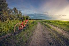 Велосипед около дороги в поле на заходе солнца стоковые фото