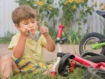 Велосипед отладки мальчика Фронт, предпосылка заднего двора Переход и дети Цикл на траве принципиальная схема детства счастливая стоковое фото