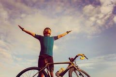 Велосипед положение велосипедиста мужское раскрывает оружия с небом утра велосипеда стоковое фото