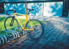 Велосипед припарковал на автостоянке велосипеда под мостом около дороги Стоковое Фото