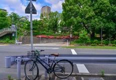 Велосипед припарковал на автостоянке велосипеда на crosswalk около дороги Стоковые Изображения