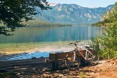Велосипед припарковал около деревянной скамьи на береге озера Bohinj Стоковое Фото