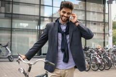 Велосипед удерживания бизнесмена и говорить на умном телефоне стоковое изображение