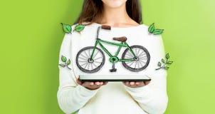 Велосипед Eco при женщина держа таблетку стоковое фото