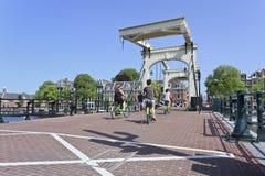 Велосипедисты на известном «тощем мосте» в Амстердам Стоковые Фото