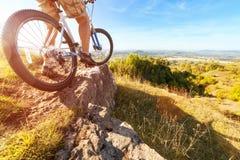 Велосипедист горы смотря покатую грунтовую дорогу Стоковая Фотография