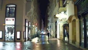 ВЕНА, АВСТРИЯ - рождество 24-ое декабря украсило узкую улицу в вечере Touristic место с магазинами и кафами Стоковое Изображение