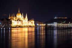 Венгерское здание парламента как увидено от Margit спрятало на ноче Стоковая Фотография