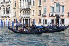 Венецианские gondoliers в гондолах с туристами на грандиозном канале, Венеции, Италии Стоковая Фотография