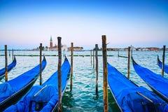 Венеция, гондолы или gondole на заходе солнца и церковь на предпосылке. Стоковая Фотография