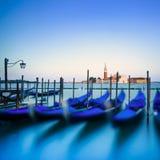 Венеция, гондолы или gondole на заходе солнца и церковь на предпосылке Стоковая Фотография