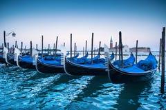 Венеция, гондолы или gondole на заходе солнца и церковь на предпосылке Стоковые Изображения