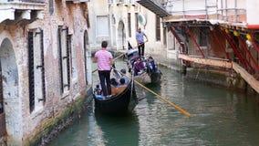 ВЕНЕЦИЯ, ИТАЛИЯ - 8-ОЕ АВГУСТА 2017 Венецианские гондолы при туристы двигая вдоль узкого канала Стоковое фото RF