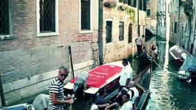 ВЕНЕЦИЯ, ИТАЛИЯ - 8-ОЕ АВГУСТА 2017 Известные венецианские гондолы проходя между старыми зданиями Стоковые Фотографии RF