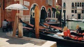 ВЕНЕЦИЯ, ИТАЛИЯ - 8-ОЕ АВГУСТА 2017 Причаленные венецианские гондолы и gondoliers принимая пролом Стоковая Фотография