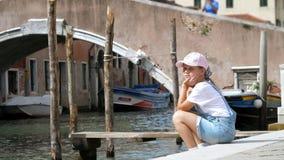 Венеция, Италия - 7-ое июля 2018: унылый ребенок девушки, в шортах и крышке сидит на береге малого канала, около моста внутри сток-видео