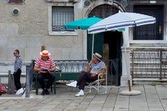 ВЕНЕЦИЯ 25-ое августа. Gondoliers на каникулах, сидя под зонтиком Стоковые Изображения