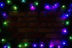 Венок и гирлянды покрашенных электрических лампочек Предпосылка рождества с светами и космосом свободного текста Граница светов р Стоковые Фотографии RF