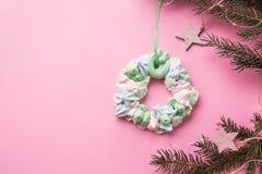 Венок меренги рождества пестротканый на ветви ели на розовой предпосылке цвета Плоское положение стоковое фото rf