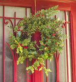 Венок падуба рождества на красной двери Стоковые Фотографии RF
