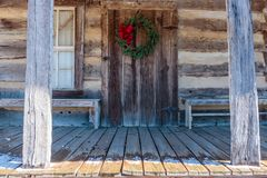 Венок рождества повешенный на двери бревенчатой хижины Стоковое Фото