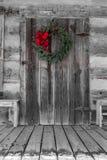 Венок рождества повешенный на двери бревенчатой хижины Стоковое Изображение RF