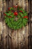 Венок рождества от хворостин сосны и красных шариков на древесине Стоковая Фотография