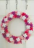 Венок рождества повиснул на белой двери в комнате в матовом тускловатом colou Стоковые Изображения RF