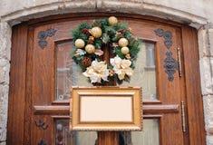 Венок рождества украшенный с шариками золота на деревянных двери и рамке с местом для вашего текста Стоковые Фото
