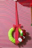Венок традиционного украшения рождества вечнозеленый с красной лентой на красной striped предпосылке Стоковая Фотография