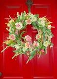 Венок цветка украшает глубоко красный покрашенный парадный вход стоковое фото