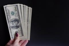Вентилятор владением руки женщины счетов на темной предпосылке 100 долларов банкнот, пакета денег, займа стоковое изображение rf