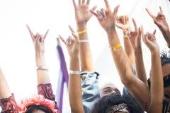 Вентиляторы показывать рожок подписывают при оружия поднятые на музыкальном фестивале стоковое изображение
