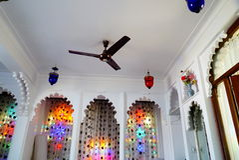 Вентилятор и красочные сдобренные окна в белой комнате Стоковые Фото