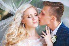 венчание Жених и невеста, целуя на красивом парке на день свадьбы , Романтичные пожененные пары Wedding пара outdoors объятие Стоковые Изображения
