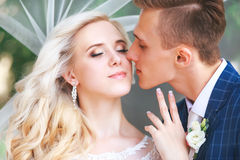 венчание Жених и невеста, целуя на красивом парке на день свадьбы , Романтичные пожененные пары Wedding пара outdoors объятие Стоковое фото RF