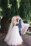 венчание Жених и невеста, целуя на красивом парке на день свадьбы , Романтичные пожененные пары Wedding пара outdoors объятие Стоковые Фотографии RF