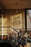 Веранда улицы открытая кафа с лестницей, велосипеда на стене и старого фонарика в Москве Стоковое Изображение