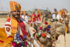 Верблюд и индийские люди нося традиционное платье Rajasthani участвуют в г-не Состязание пустыни как часть фестиваля пустыни в Ja Стоковое Изображение
