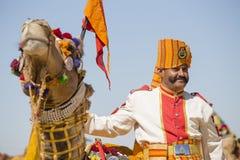 Верблюд и индийские люди нося традиционное платье Rajasthani участвуют в г-не Состязание пустыни как часть фестиваля пустыни в Ja Стоковые Фото