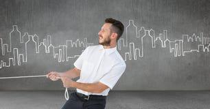 Веревочка бизнесмена вытягивая в комнате с чертежами города Стоковая Фотография