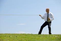 Веревочка бизнесмена вытягивая в парке Стоковая Фотография RF
