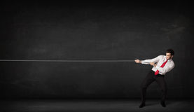 Веревочка бизнесмена вытягивая на серой предпосылке Стоковое Изображение RF