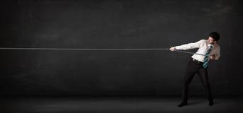 Веревочка бизнесмена вытягивая на серой предпосылке Стоковые Изображения RF