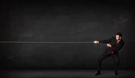 Веревочка бизнесмена вытягивая на серой предпосылке Стоковые Фото