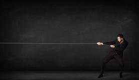 Веревочка бизнесмена вытягивая на серой предпосылке Стоковые Изображения