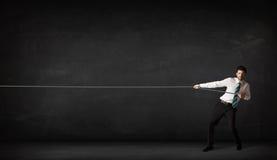 Веревочка бизнесмена вытягивая на серой предпосылке Стоковое фото RF