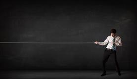 Веревочка бизнесмена вытягивая на серой предпосылке Стоковое Изображение