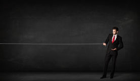 Веревочка бизнесмена вытягивая на серой предпосылке Стоковая Фотография RF